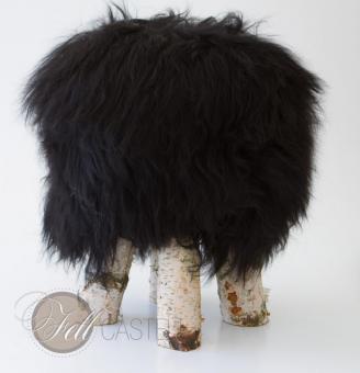Fellhocker mit Island Schaffell Bezug Schwarz 55 cm hoch Birkenholz Beine